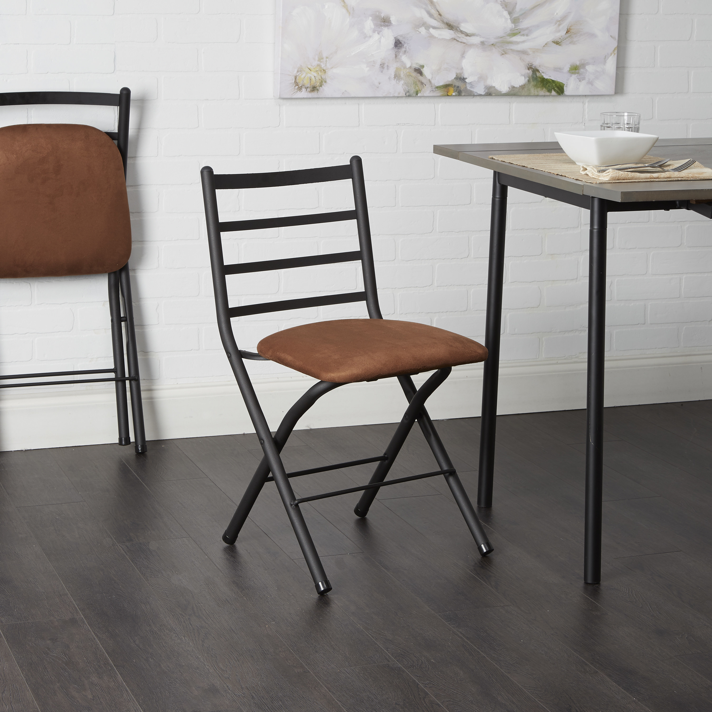 The chair, with black tube body and brown microfiber padded seat