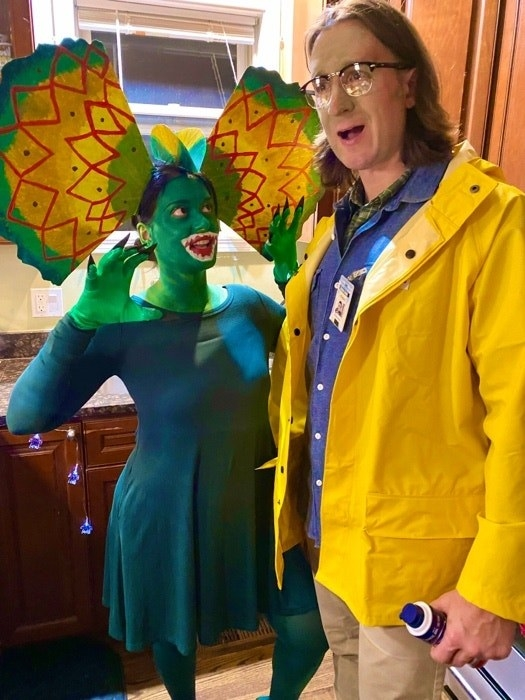 Someone dressed as Dennis Nedry in his iconic yellow jacket, and another person dressed as a Diophosaur, green paint and all
