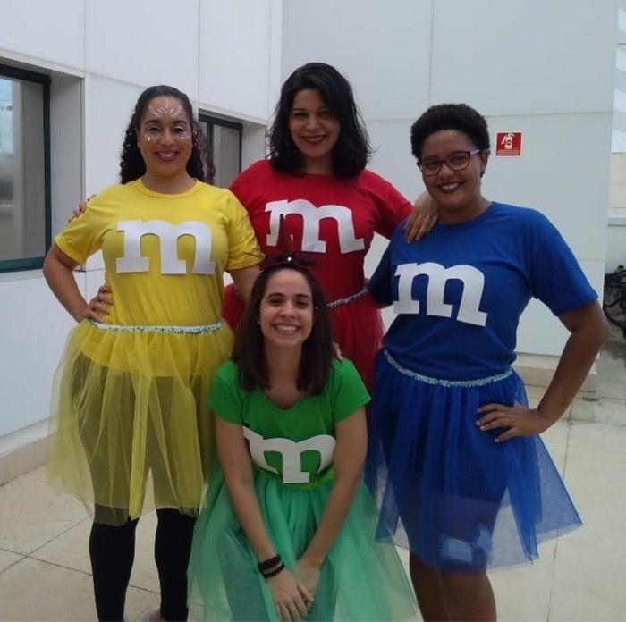 Four people, each dressed as a differently colored MM