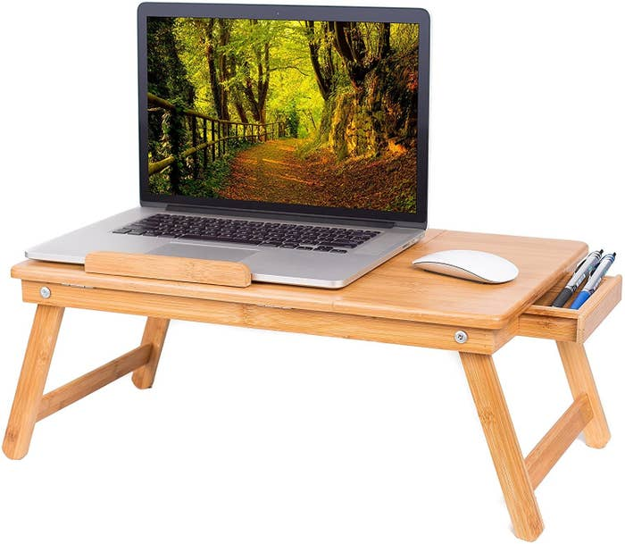 The lap desk has space for a laptop and a mouse. It also has a drawer for writing utensils