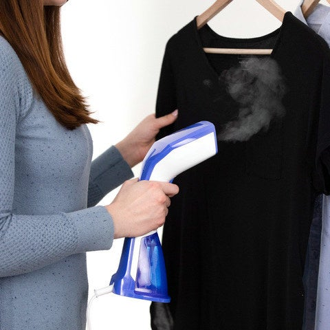 The steamer, which is blue and white plastic and fits in the hand, steaming a shirt hanging from a rack