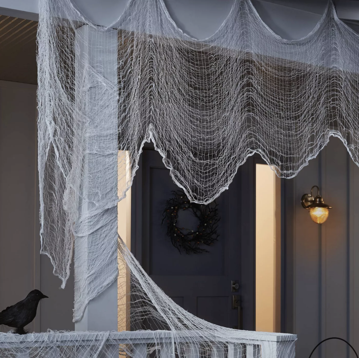 The white net fabric draped around a porch to look like webs