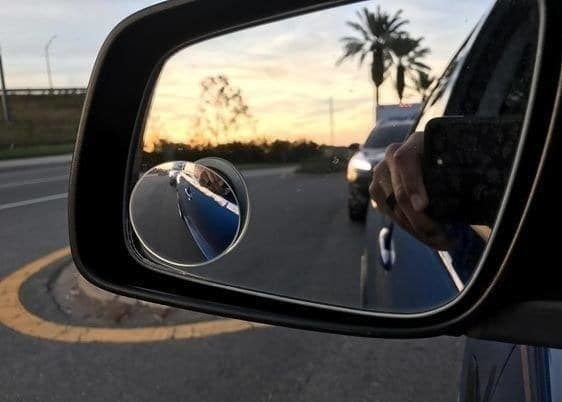 The blind spot mirror attached to a rearview mirror showing more closely, how much room is next to the car door