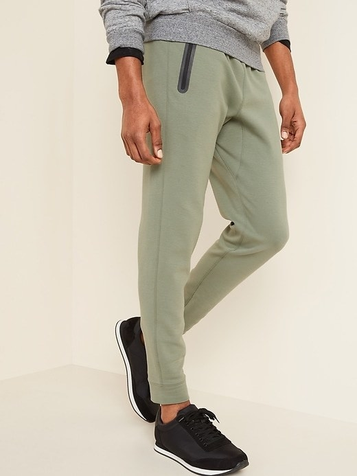 Model wearing the joggers in money maker green with a grey sweatshirt and black sneakers