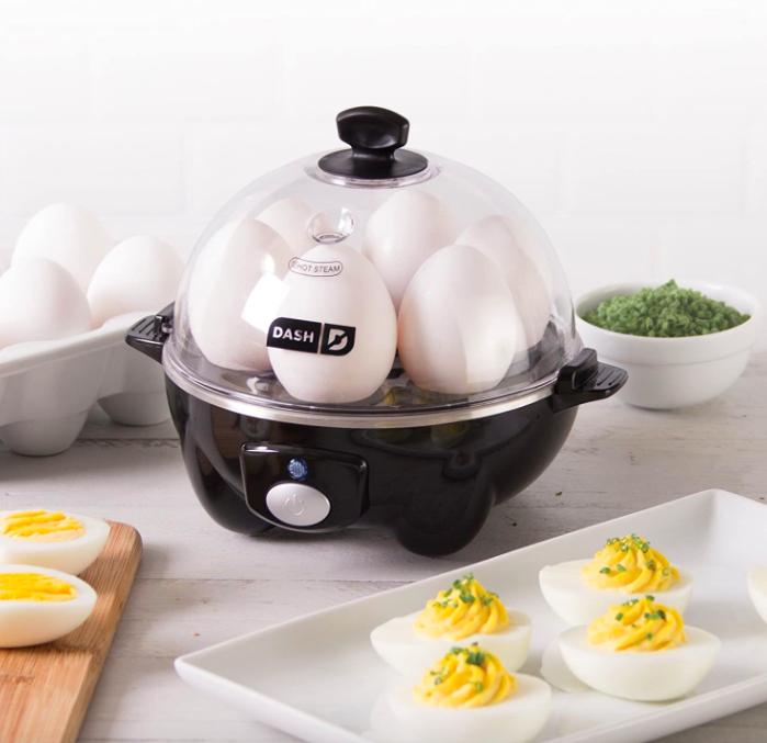 Black Dash Rapid Egg Cooker heating up six hard-boiled eggs next to a white dray with deviled eggs
