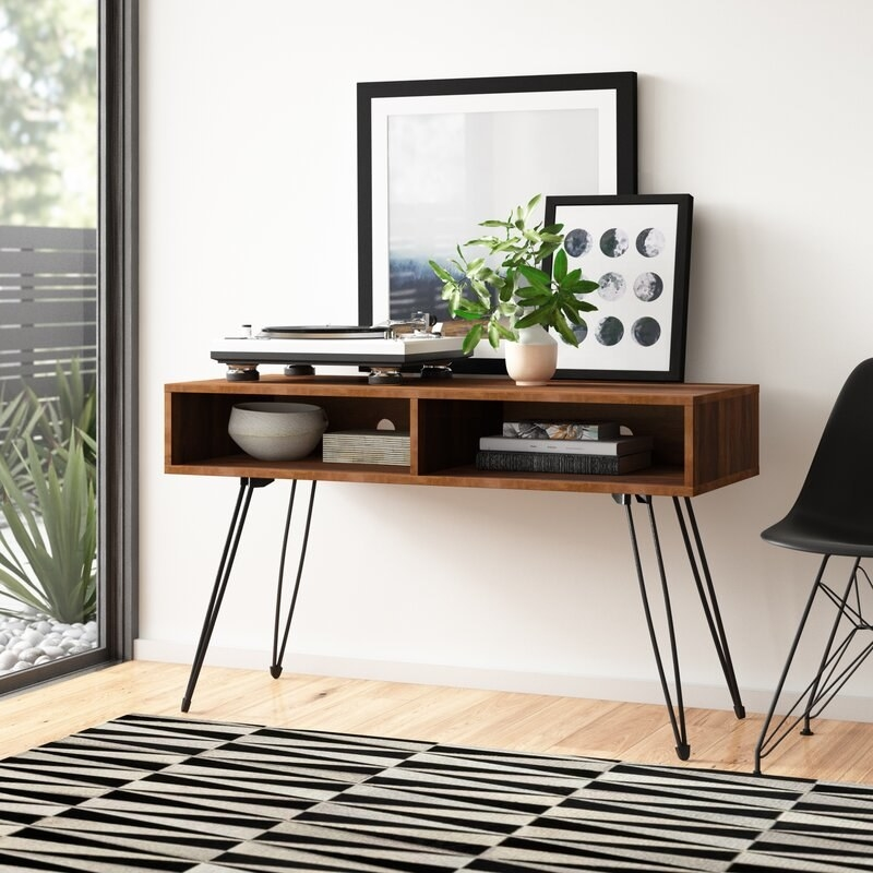 the brown TV stand with black legs