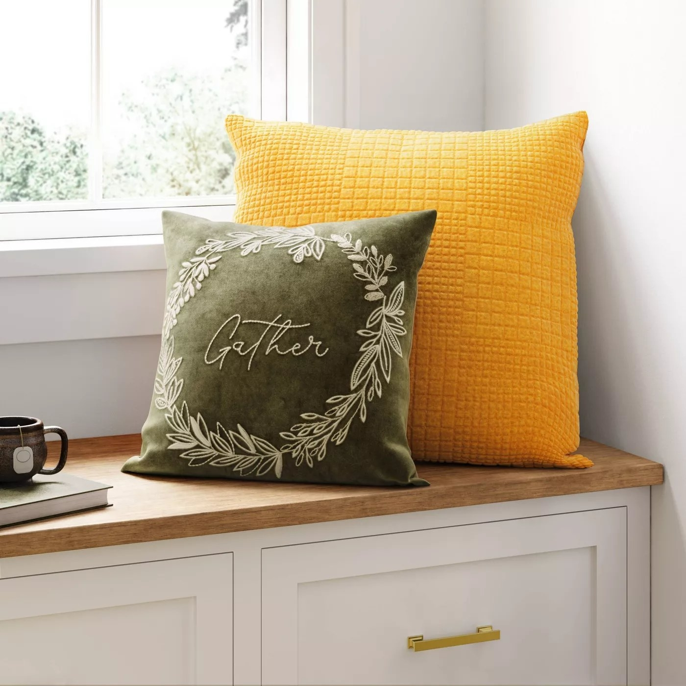 """The pillow with the word """"Gather"""" written on it in white inside a matching circular leaf design"""