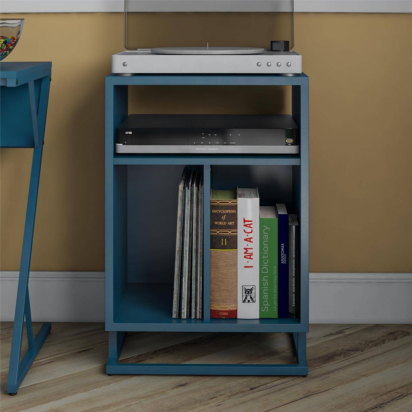 The record stand in blue, with three storage areas — a large bottom shelf, big enough to hold vinyl, divided in half; a smaller cubby above it; and a top area, where you can place your turntable