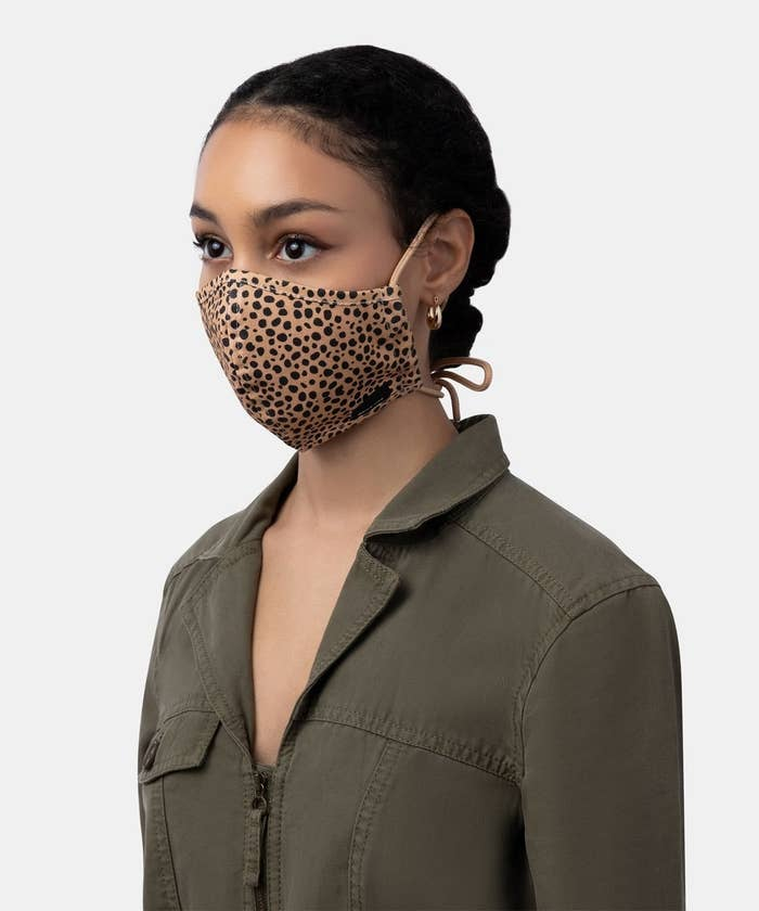 model wears tan mask with black spots with tie back