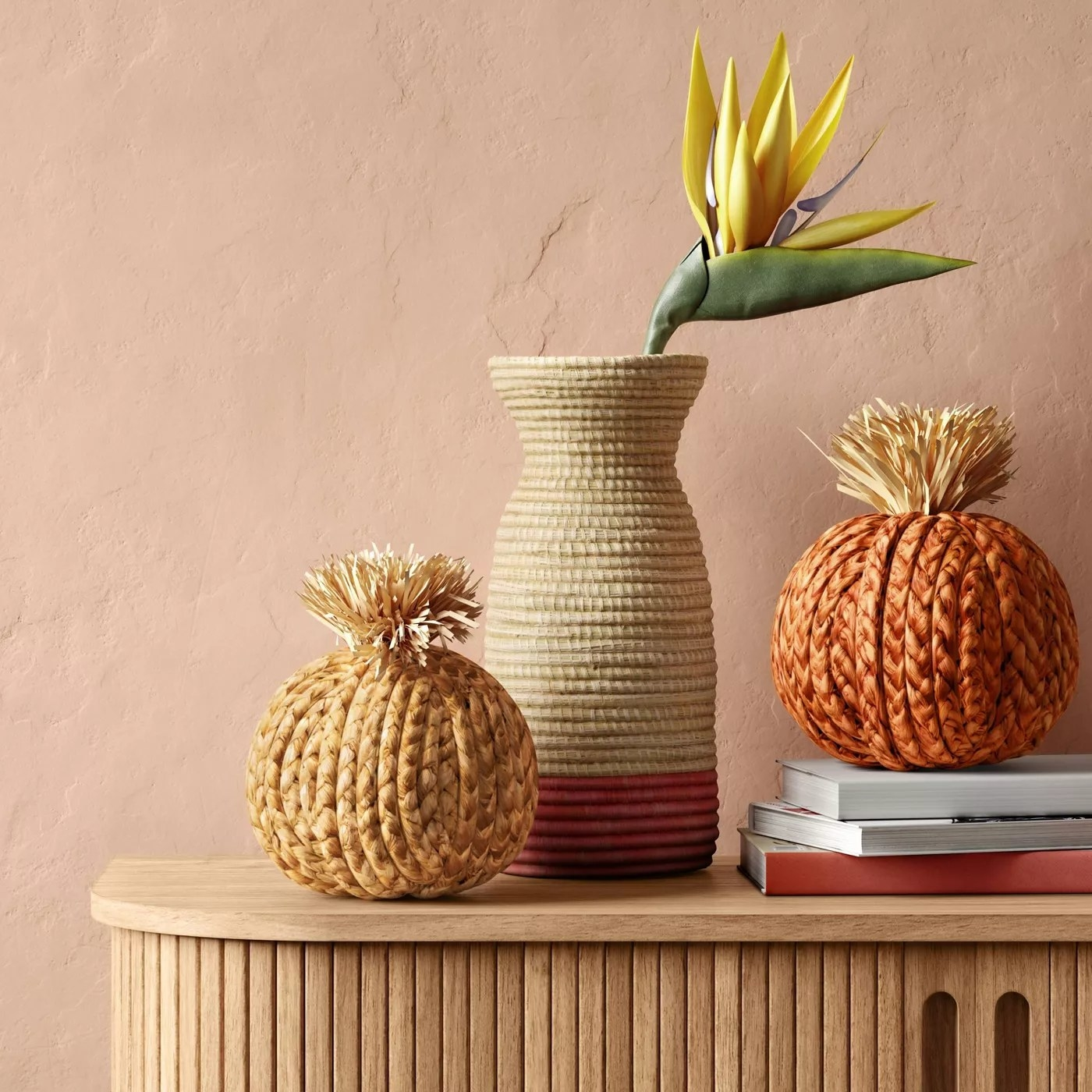 A natural-colored pumpkin and an orange pumpkin on an entryway table