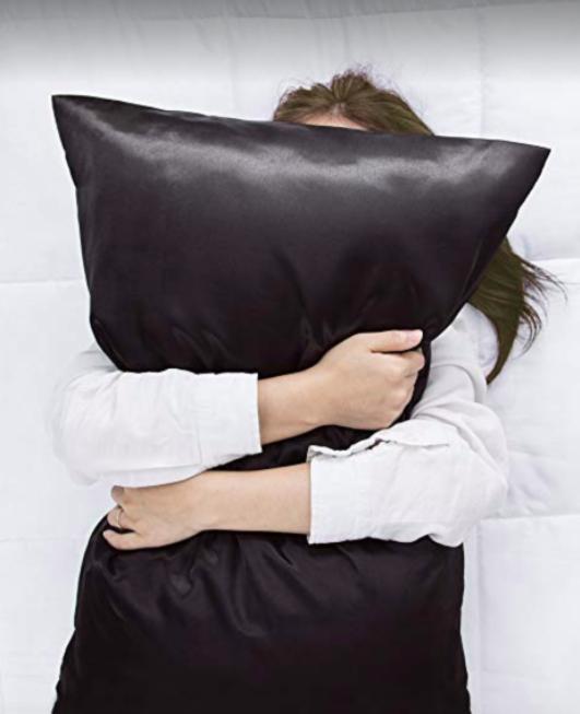 Model hugs black satin pillowcase while wearing a white shirt