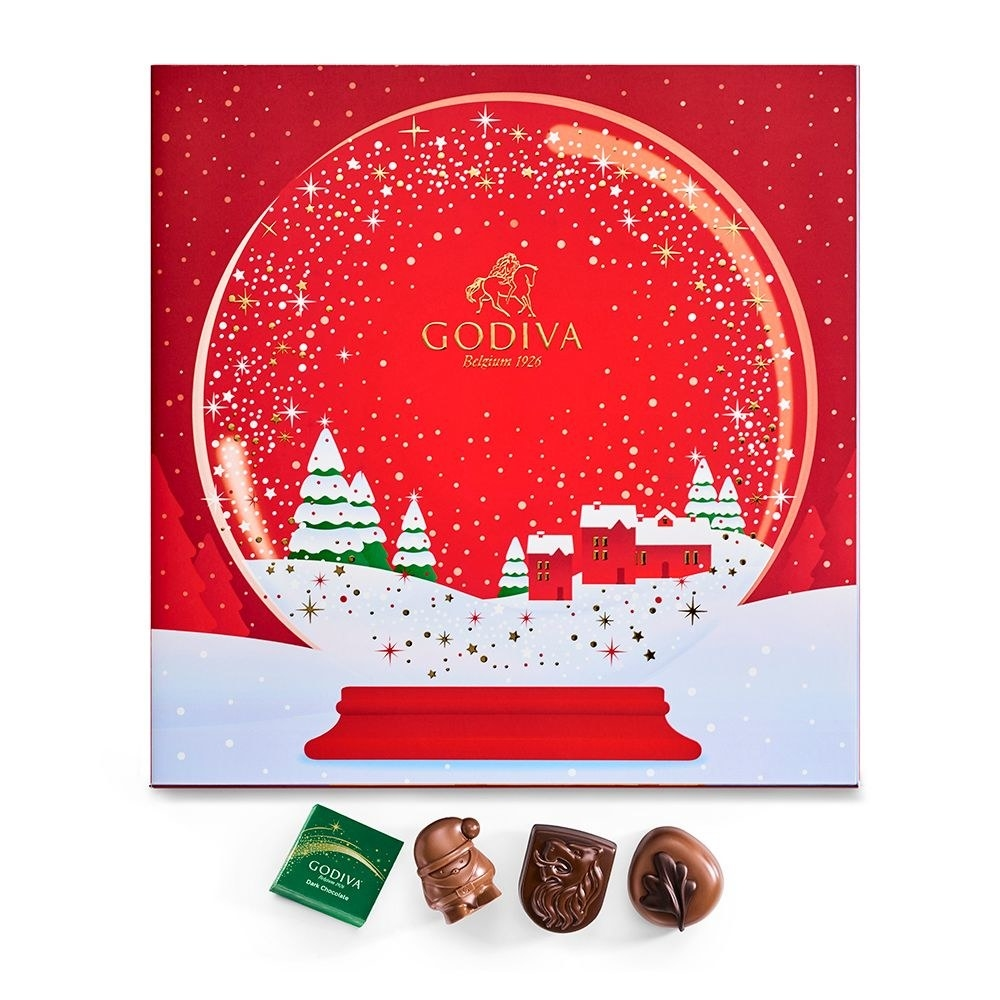 a cardboard advent calendar with the design of a snow globe on it that opens to reveal individual windows of chocolate
