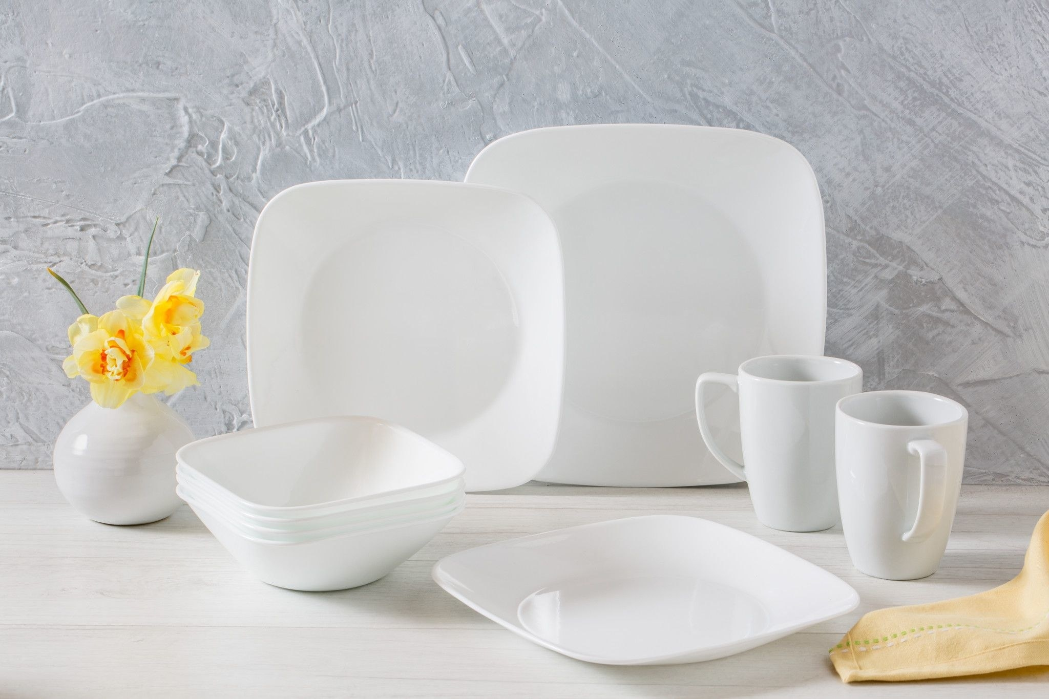 Some of the dinnerware from the set, including two mugs, square plates and square bowls, all in white