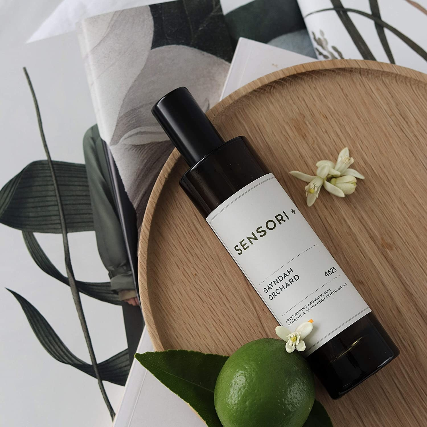 A bottle of Sensori air mist lies on a wooden plate surrounded by white flowers, limes and leaves