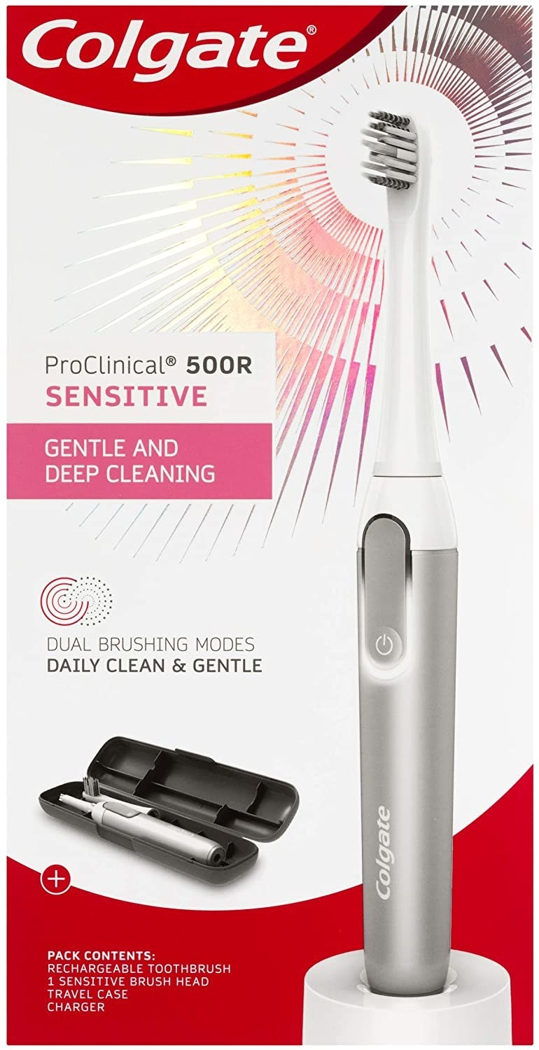 A grey and white electric toothbrush on red Colgate packaging