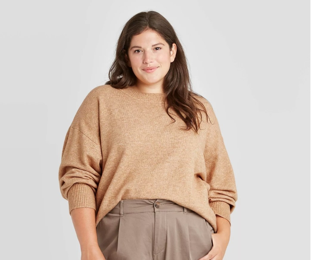 Model wearing slouchy tan colored, pullover sweater