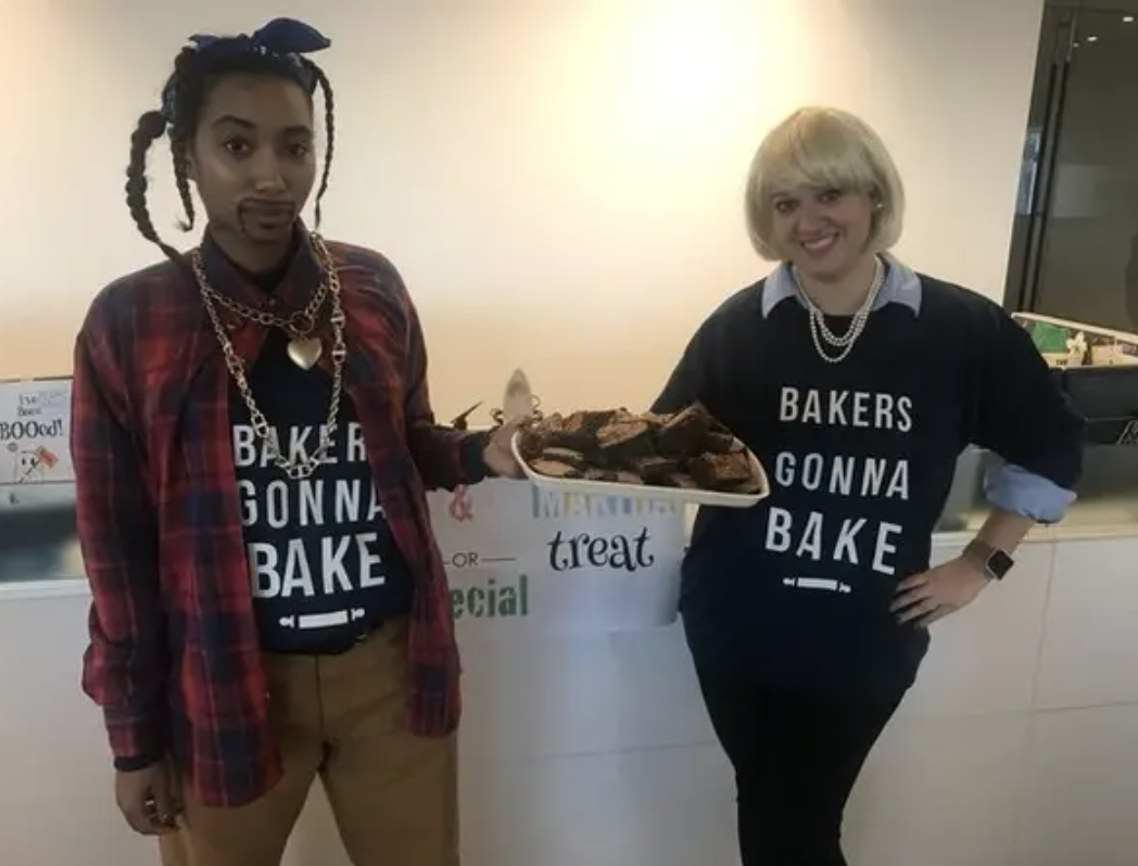 "Two people dressed as Snoop Dogg and Martha Stewart, holding a tray of brownies, and wearing shirts that read ""bakers gonna bake"""