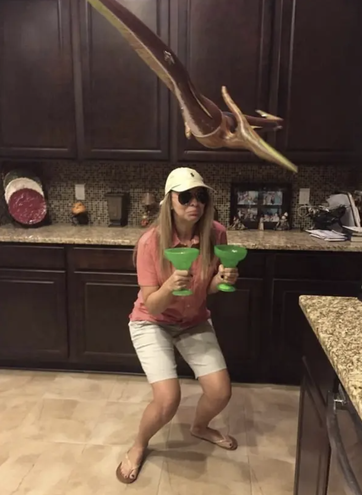 Someone dressed in summer clothes, holding two margarita glasses, with a fake dinosaur flying over head