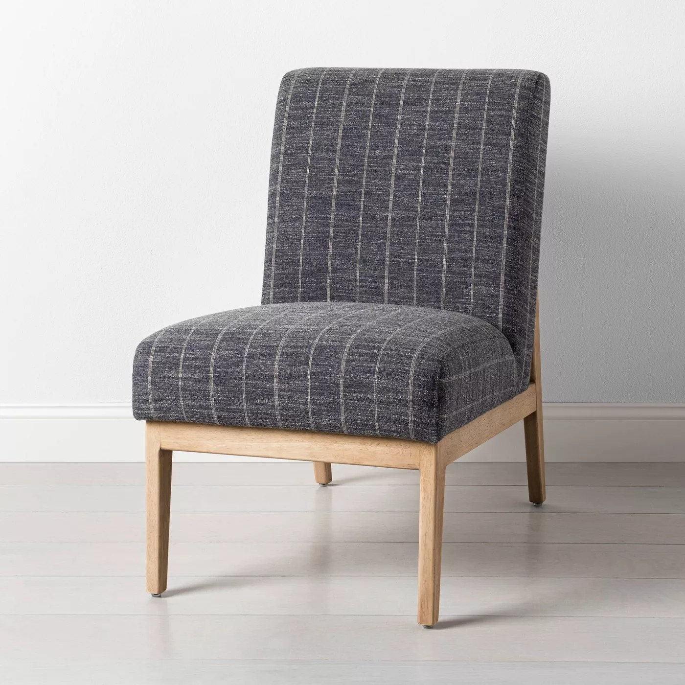 The armless chair with a gray striped fabric and light wood frame
