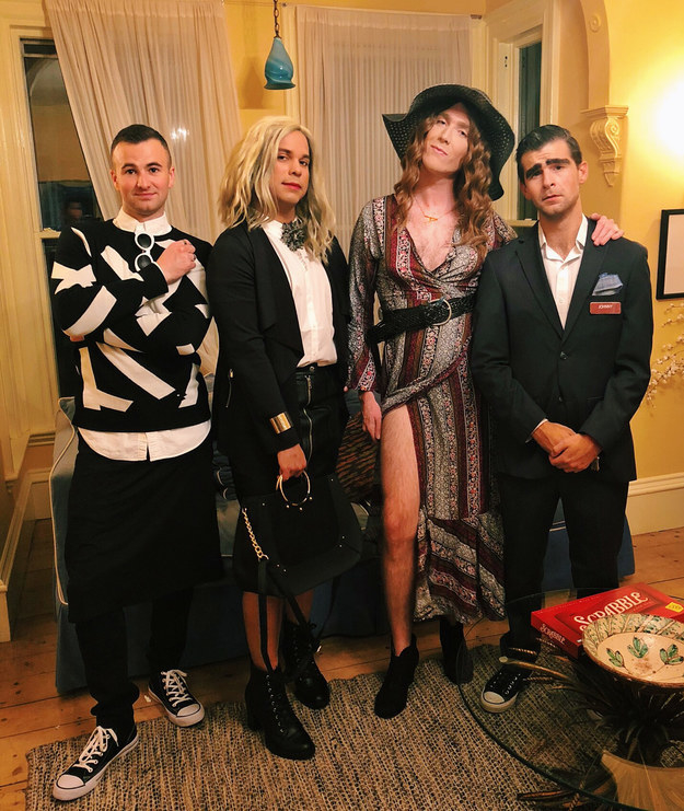 Four people standing side-by-side. The first is David, wearing a printed sweater and holding sunglasses. The second is Moira with a wig, and chic outfit. Third is Alexis with a wig and dress with a thigh slit. Then Johnny with a suit and fake eyebrows.