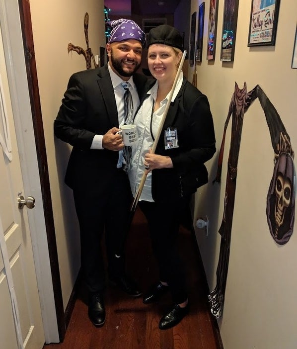 "Two people standing next to each other in suits. One is wearing a bandana on their head and holding a ""World's Best Boss"" mug, and the other is wearing a newsboy hat and holding a players cue."