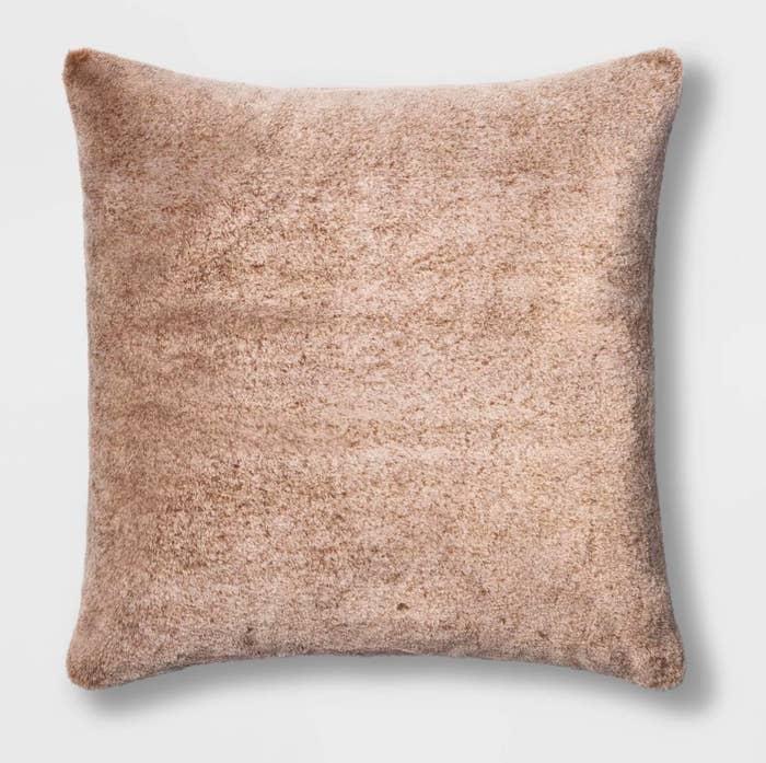 The tan throw pillow