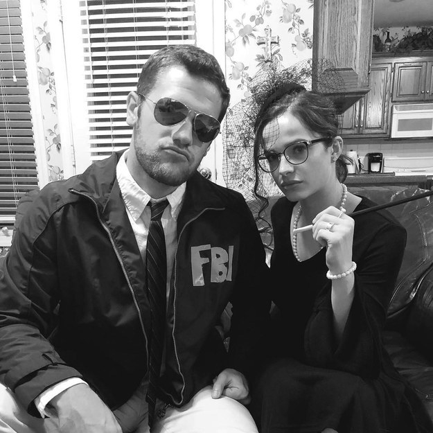 A man with sunglasses and an FBI jacket and a woman with a pearl necklace, snood on her head, and cigarette holder in her hand.