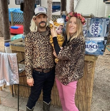 A man with a wig, hat, and fake moustache and a woman with a flower crown holding a baby dressed as a tiger.