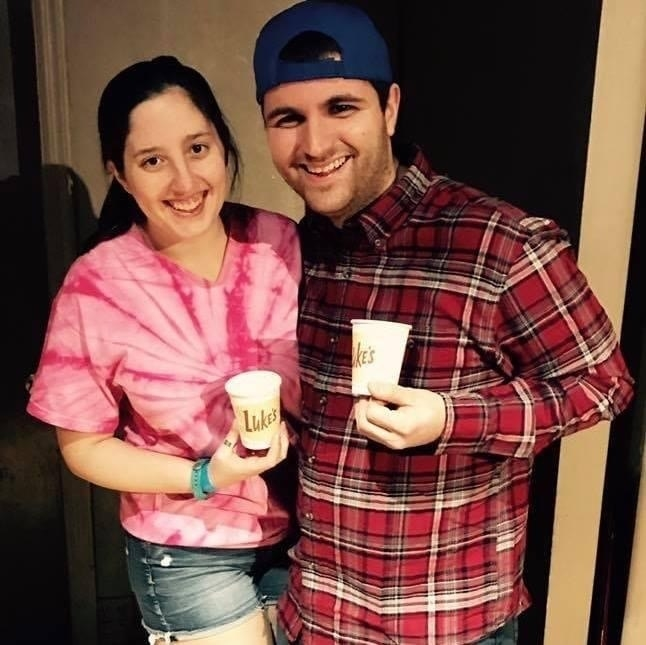 "A woman in a tie dye shirt with jean shorts, holding a ""Luke's"" coffee cup. A man next to her is wearing a baseball cap, a flannel shirt, and also holding a coffee cup."