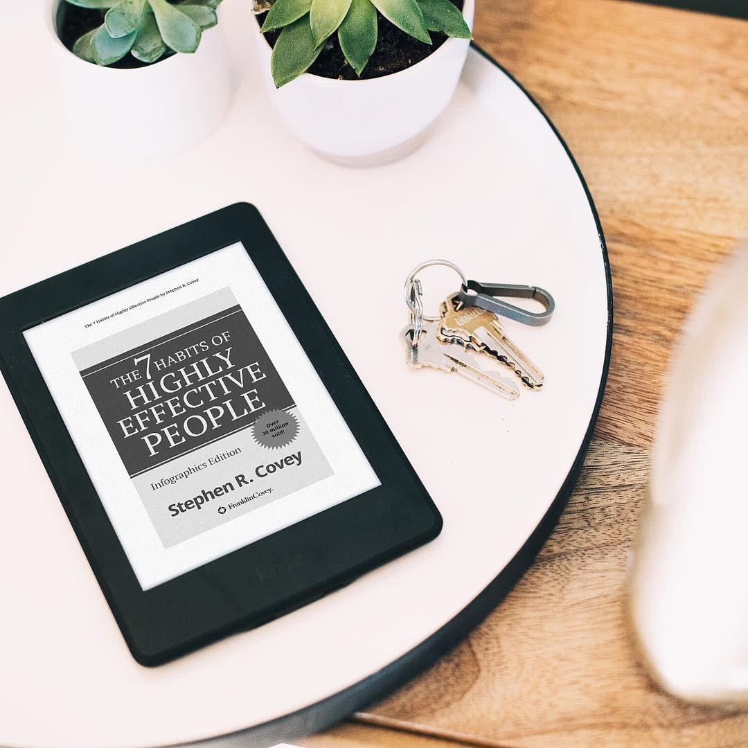 A Kindle on a table next to a set of keys
