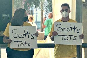 People holding up Scott's Tots signs