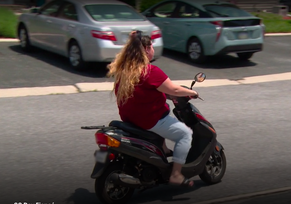 Natalie zooms off on a moped