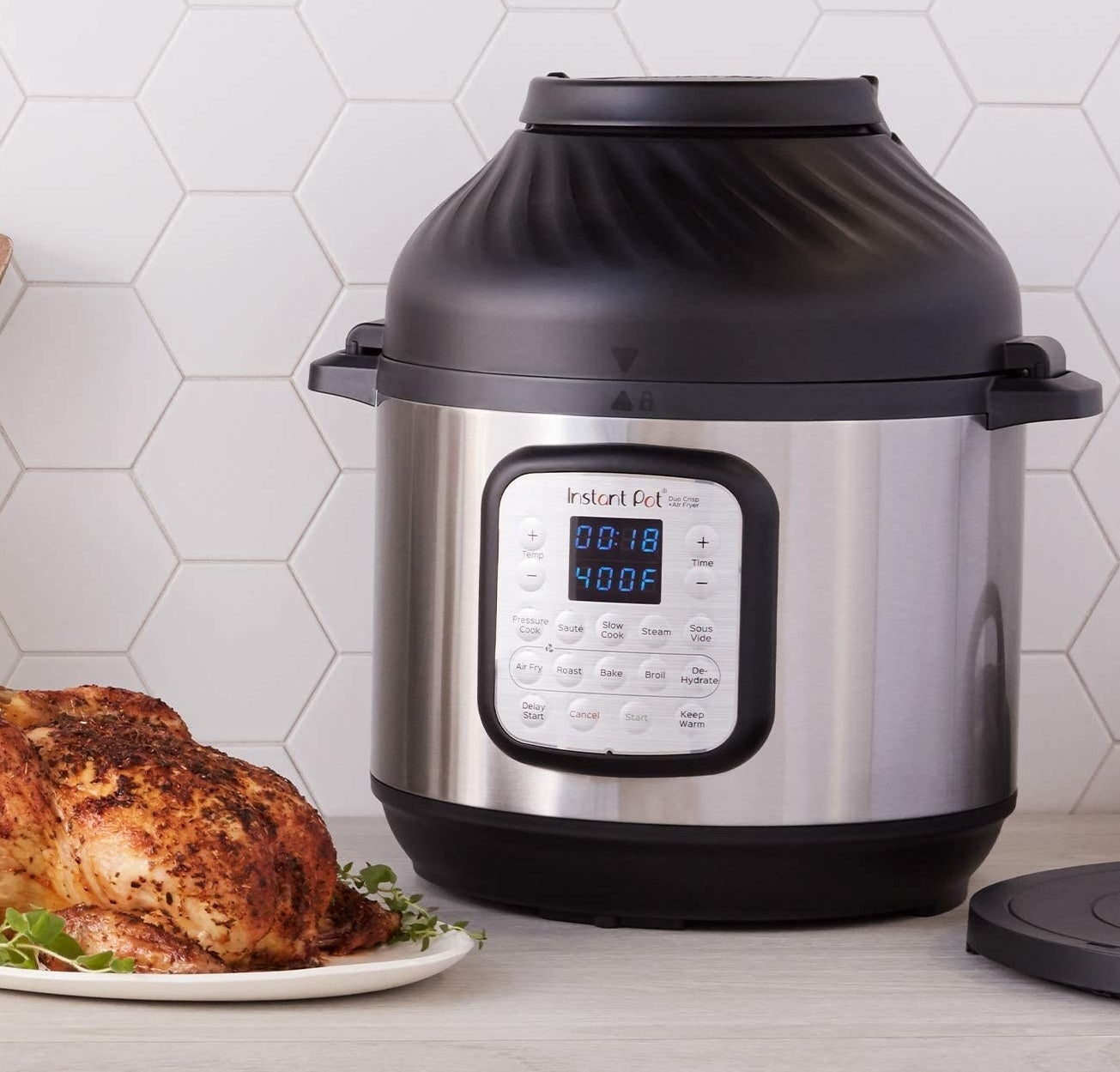An InstantPot next to a cooked chicken