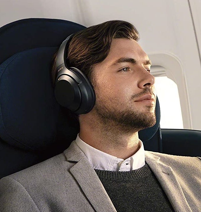 A person listening to the headphones on a plane