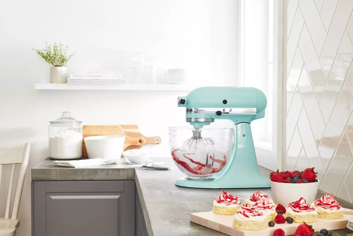 The ice-green, tilt-head Kitchenaid with a glass bowl that has measurement markings on the side