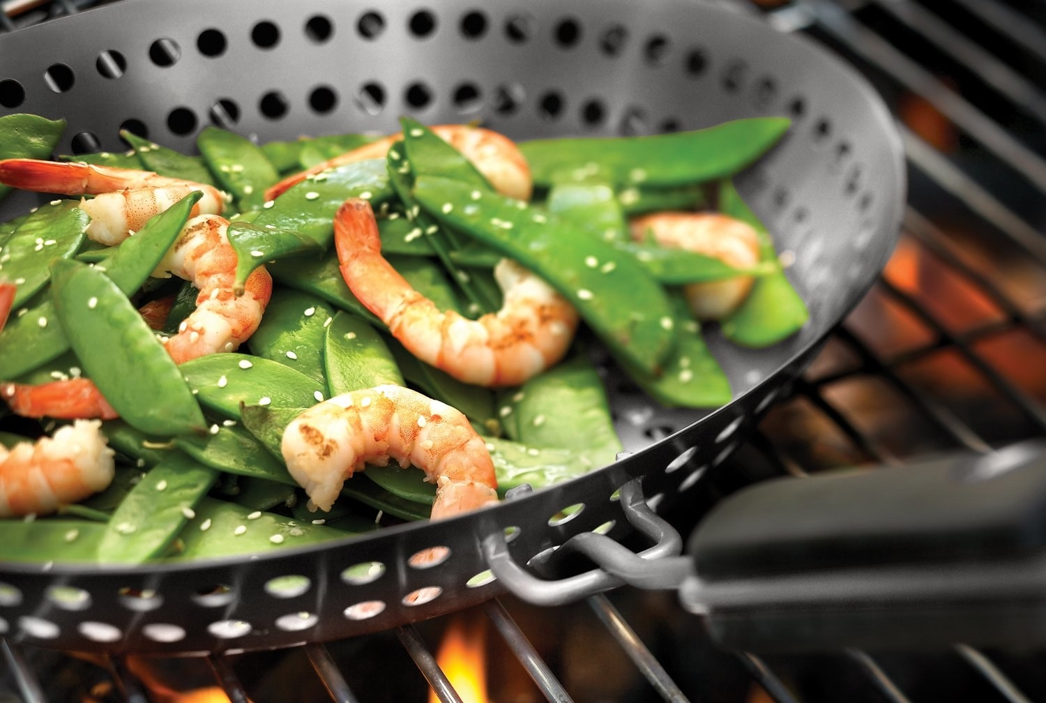 Shrimp and beans being cooked on a grill in a pan with perforations