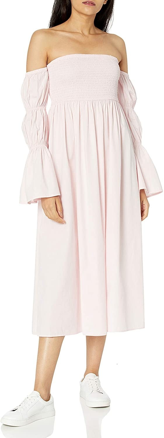 Model in the long sleeve midi dress in pink with smocked bodice