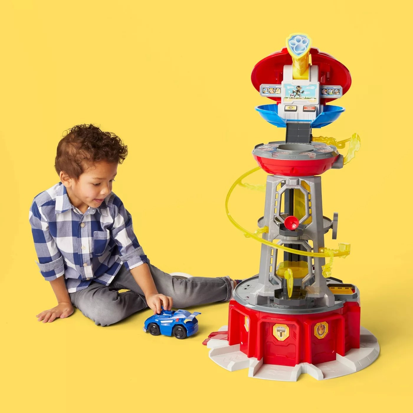 A child playing with a car next to the Paw Patrol lookout tower