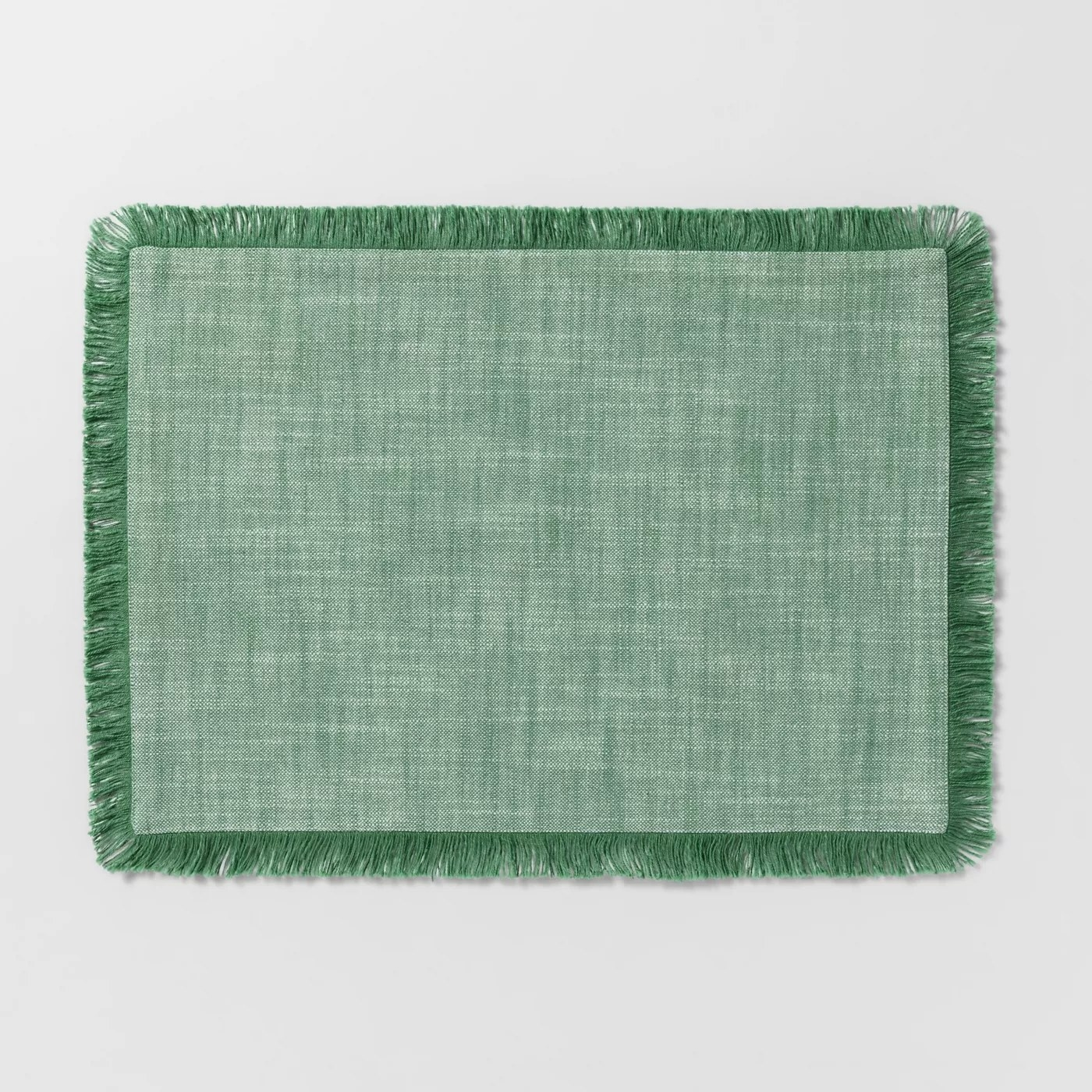 The green chambray placemat with a fringed edge