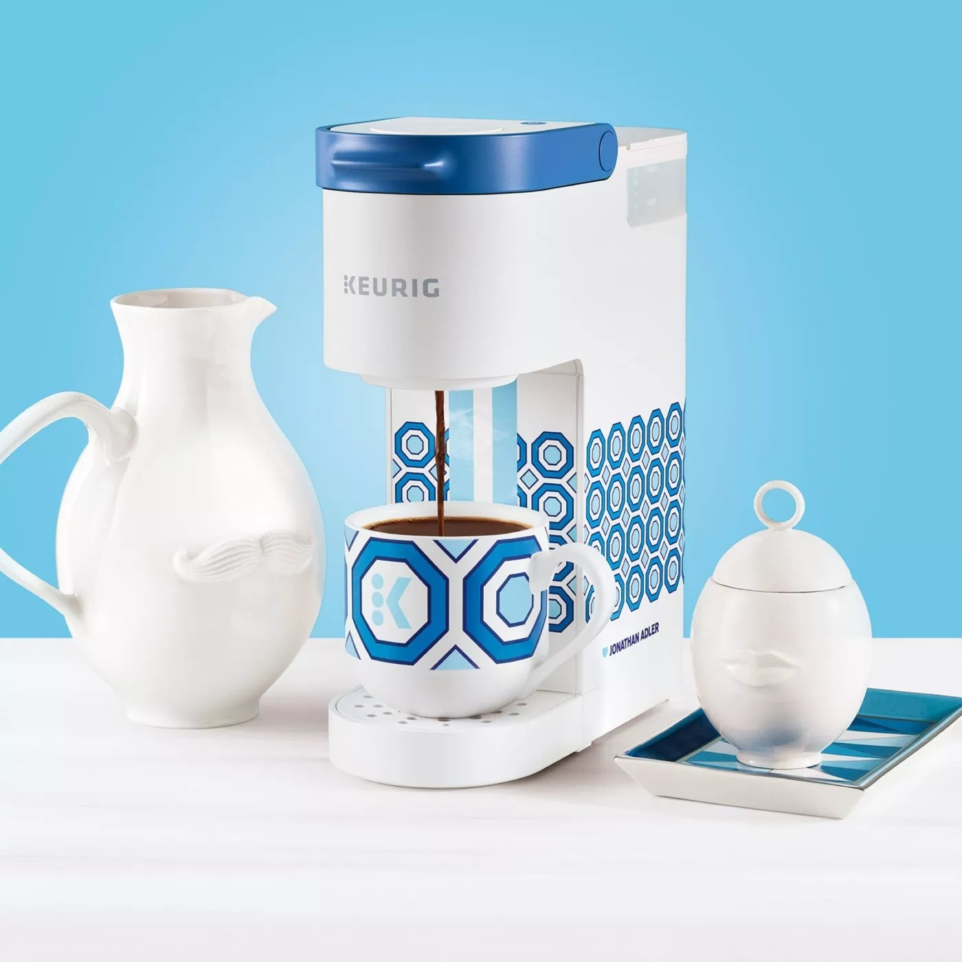 The white-and-blue, hexagon-patterned Keurig coffee maker and the matching coffee mug