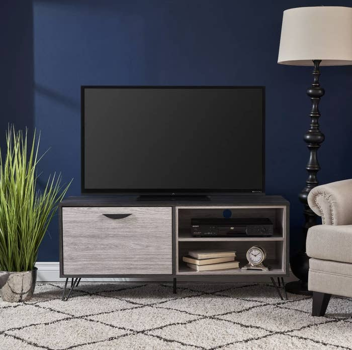 A TV stand with a tv on top in a living room