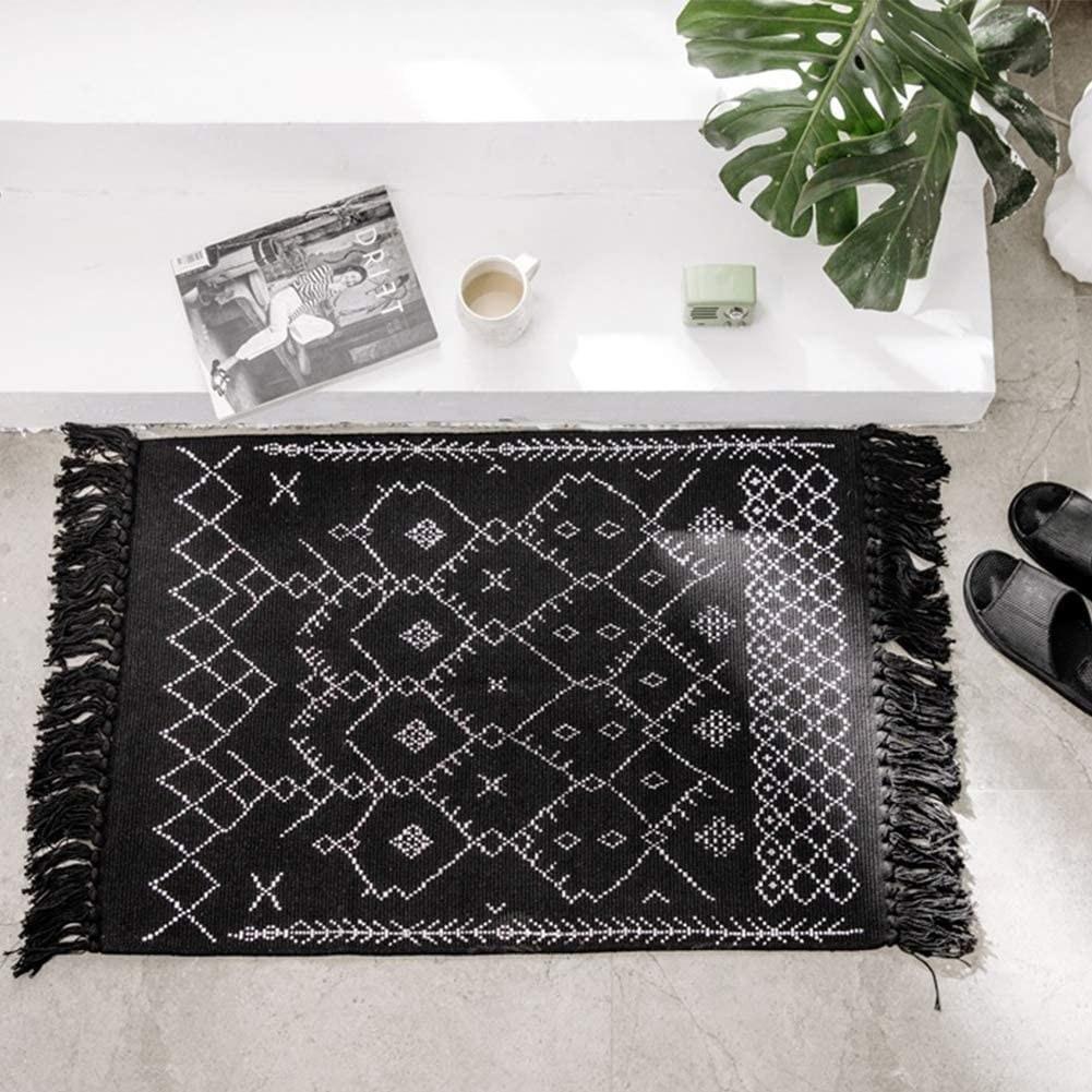 Black tassel rug with geometric tribal pattern in white