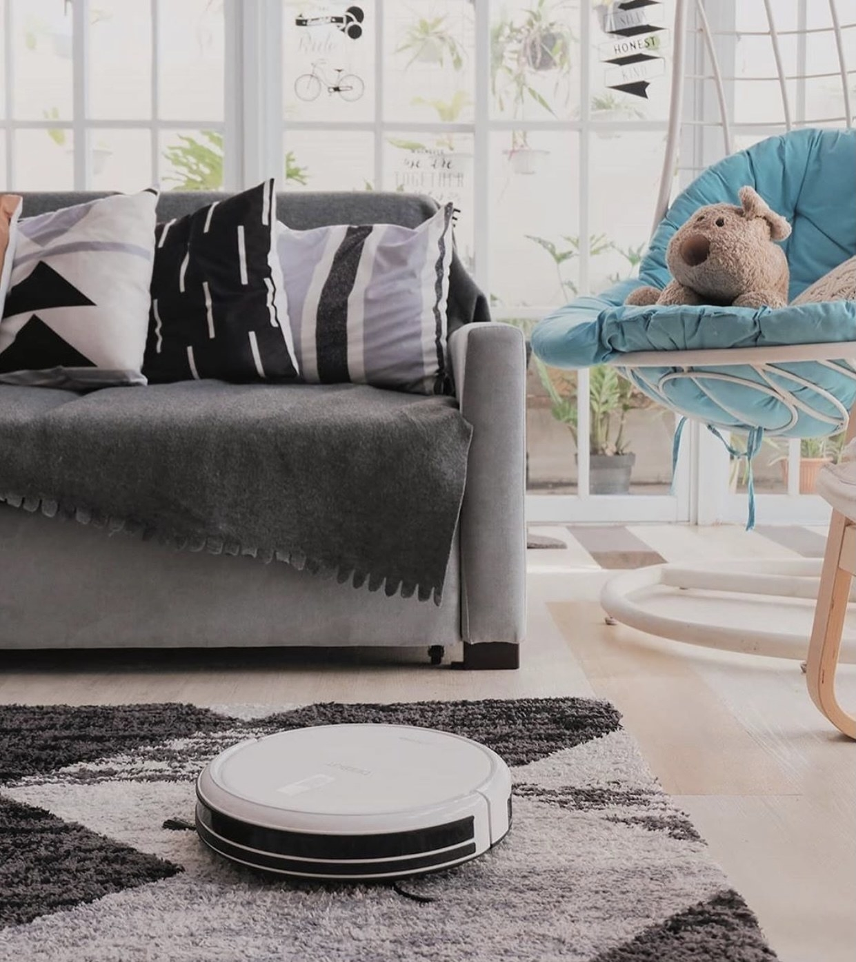 A white robotic vacuum cleans a carpet in a living room