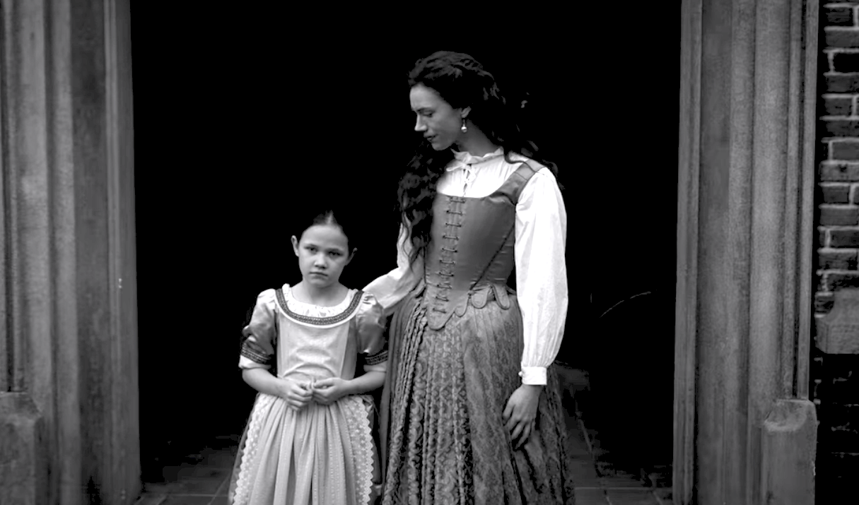 A black and white image of a woman and a young girl standing in front of a front door in old timey clothes