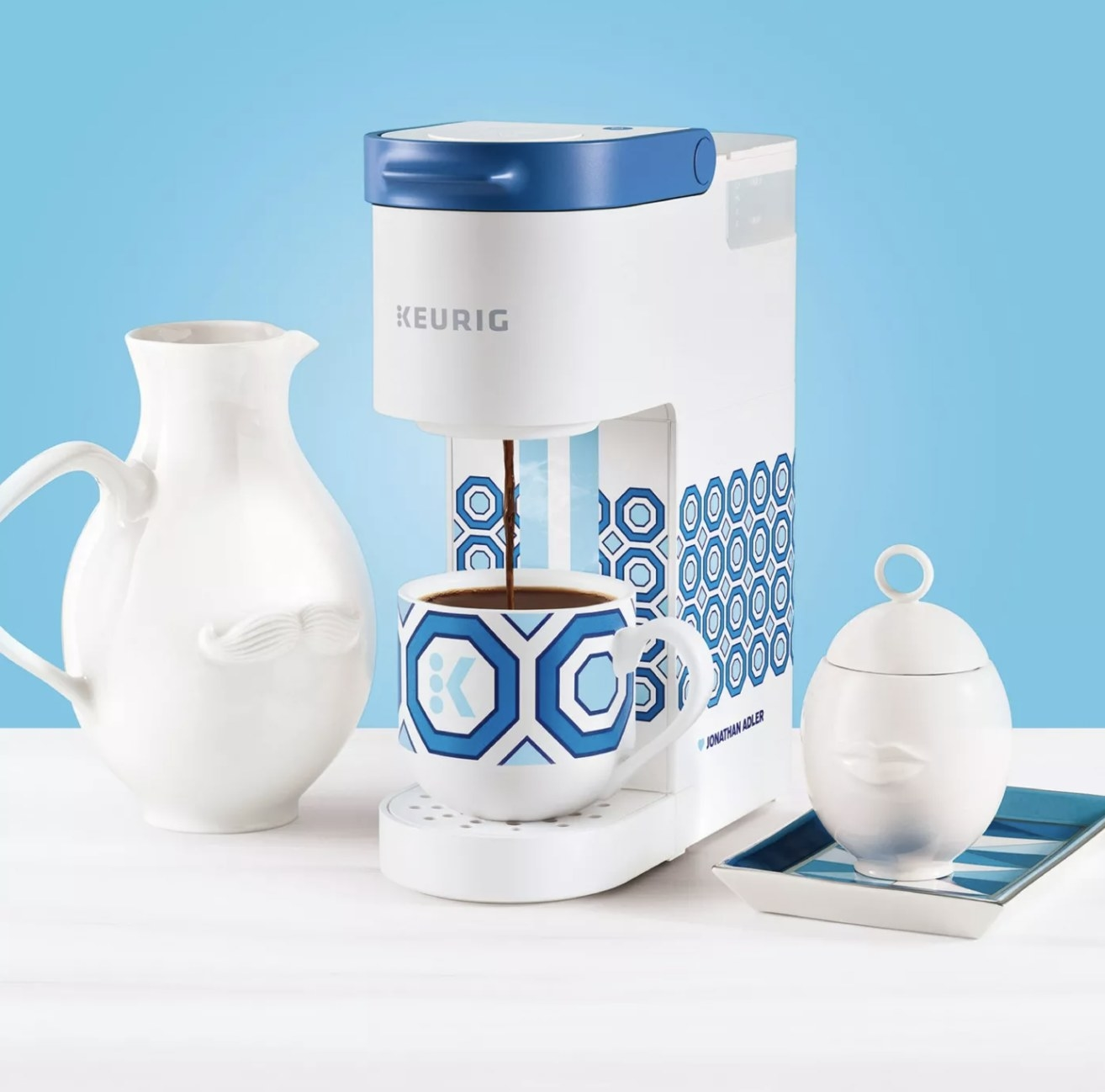 A white single-serve Keurig with blue geometric patterns throughout pouring coffee into a mug