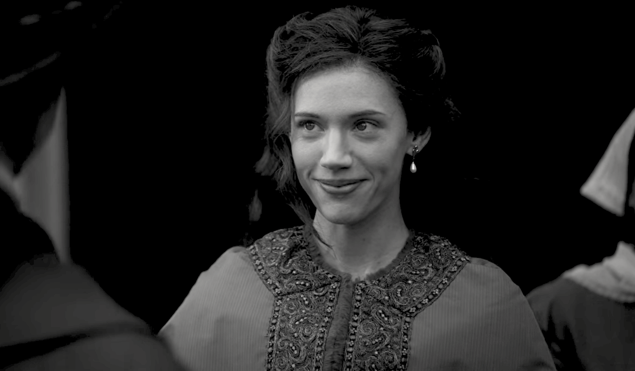 A black and white image of a woman smiling slightly at someone off screen