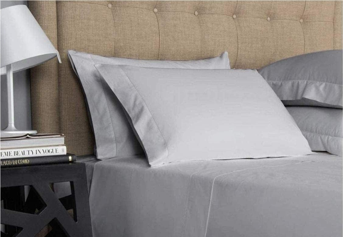 A close up of the smooth sheets on a neatly made bed