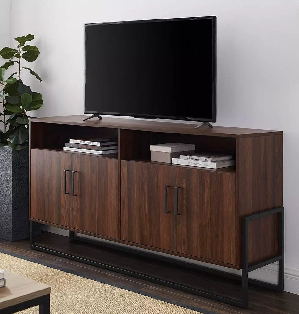 A brown, wood-composite TV stand with four cabinet doors, two open shelves, and black hardware