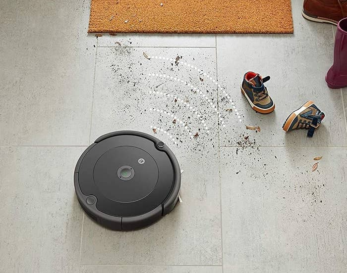 A roomba cleaning up dirt in an entryway