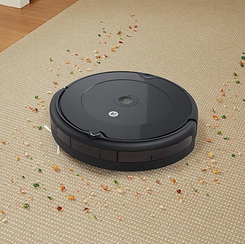 A Roomba cleaning crumbs off a carpet
